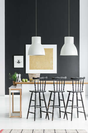 White lamps above countertop with black bar stools in kitchen with gold painting on black wall