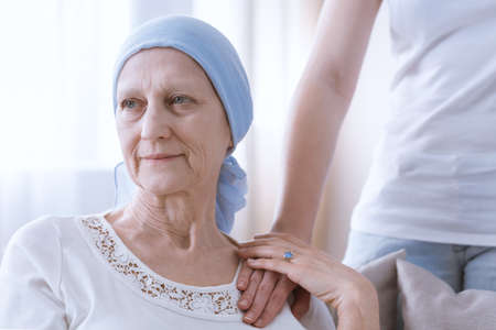 Hopeful woman battling with cancer wearing blue headscarf getting support Stock Photo