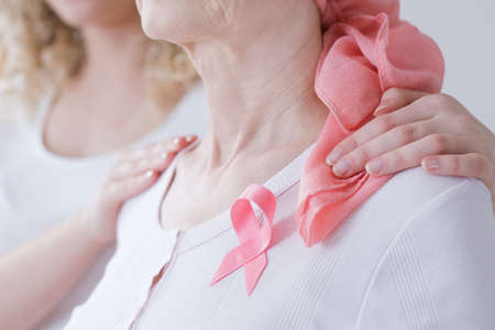 Smiling daughter encouraging mother diagnosed with cancer