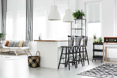 Panier tressé au sol à côté du comptoir de cuisine avec tabourets de bar dans la chambre avec radio vintage sur étagère Banque d'images - 85015651