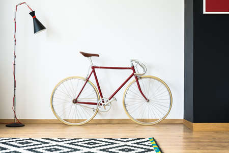 Red bike in simple living room with design lamp and patterned black and white carpet Stock Photo