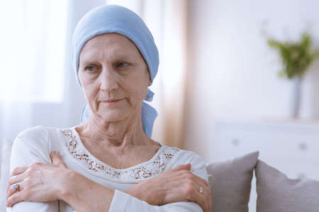 Sad depressed woman suffering from malignant breast cancer sitting alone Stock Photo