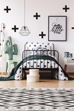 Zwart en wit geometrisch tapijt in kinderkamer met speelgoed op stoel naast bed met grijs kussen