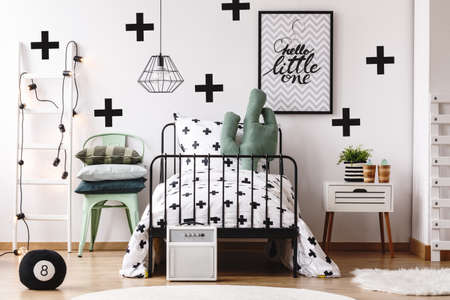 bedside: Cactus pillow on bed with patterned overlay in kids room with white ladder and poster on wall Stock Photo