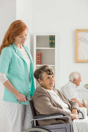 Assistant looks on elder woman on wheelchair in common room for seniors