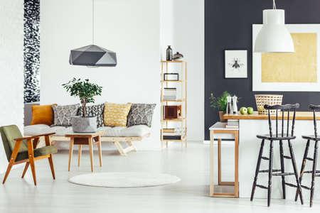 Tabouret de bar sur le comptoir de cuisine dans un intérieur multifonctionnel avec chaise verte et canapé Banque d'images - 84999994