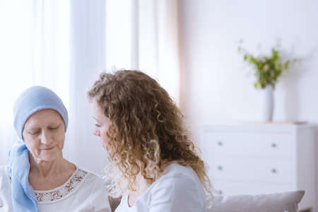 Young woman talking with sick mother battling with malignant cancer Stock Photo