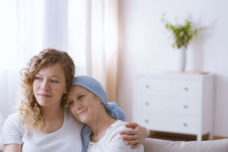 Hopeful smiling woman battling with cancer hugging daughter Stock Photo