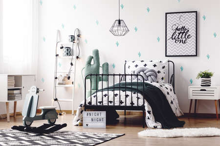 bedside: Wood rocking toy on geometric carpet in scandi kids room with bed and white ladder