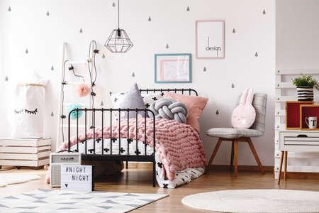 De kleurrijke hoofdkussens breien roze deken op bed in leuke jonge geitjeslaapkamer met affiches op muur Stockfoto - 85015667