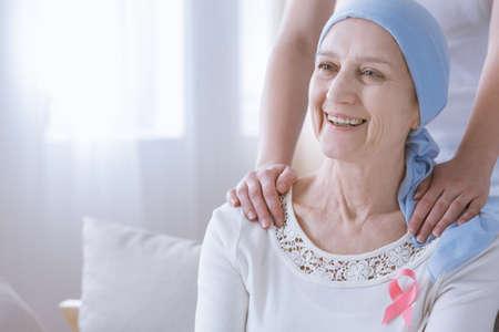 Glimlachende vrouw met borstkanker dragen roze lint op de borst Stockfoto