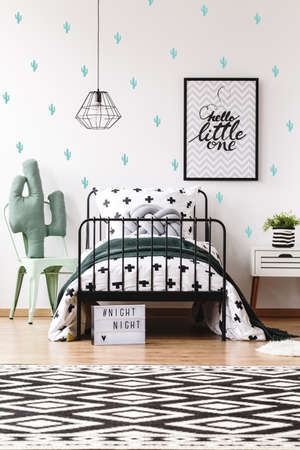 bedside: Cactus toy on chair next to bed in scandinavian style kids room with geometric carpet Stock Photo