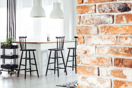 Red brick wall in rustic dining room with white lamps above countertop with black bar stools