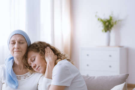 Sick woman with headscarf suffering from cancer hugging daughter Stock Photo - 85585772