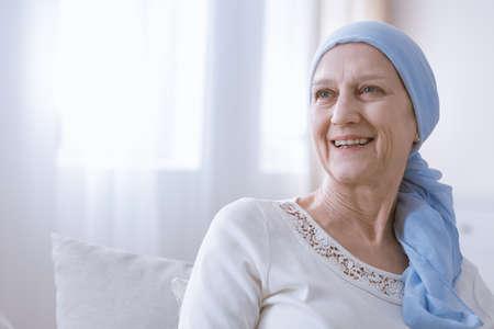Gelukkige vrouw met kanker in blauwe hoofddoek lachend met hoop
