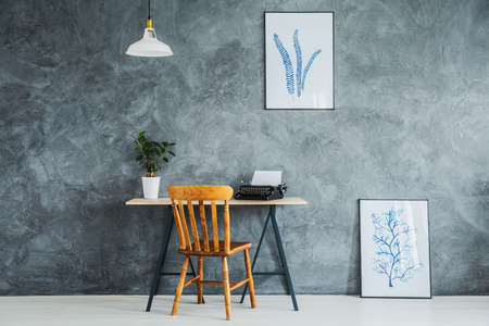 Textured wall with two posters with blue sketches and minimal desk with wooden chair