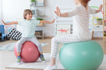 Physiotherapist and young boy doing stretching exercise on colorful balls in bright room