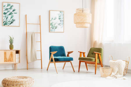 Two vintage chairs in bright room with ladder, pouf and paintings with floral motif on white wall Imagens