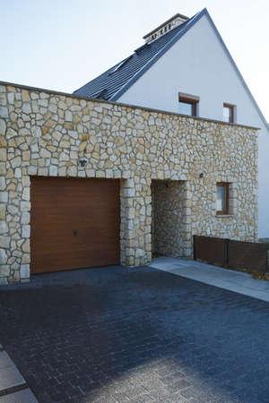 大きなモダンな家の木製ガレージドアのドア、レンガの入り口