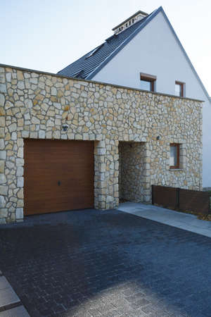 Wooden garage door and brick entrance of big modern house Stok Fotoğraf