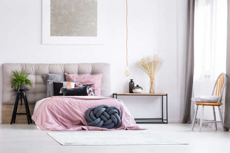 king fern: Black braided pillow and pink overlay on king-size bed in trendy bedroom with orange chair and copper lamp