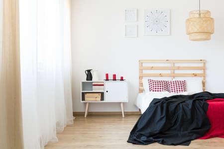 Houten hoofdeinde en rode accenten in de slaapkamer