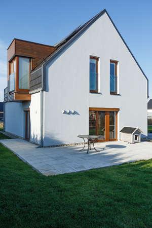 舗装されたテラス、緑の芝生と太陽光パネルと家族の家 写真素材