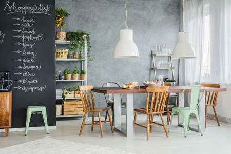Modern dining space with shopping list on chalkboard wall