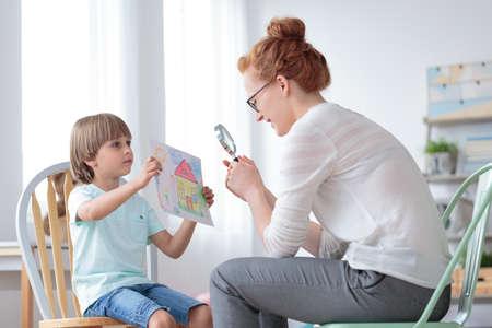 孤児の少年によって示された完璧な家の写真を虫眼鏡で見る養子縁組カウンセラー 写真素材 - 85134045