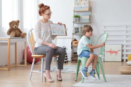 Red haired counselor talking about adoption with sad boy sitting on mint chair Stock Photo