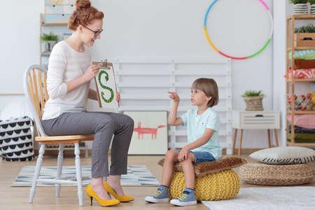 음성 치료사와 함께 수업 중에 올바른 발음을 연습하는 노란색 pouf에 앉아있는 소년