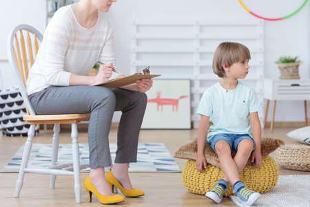 Misbehaving boy sitting on a yellow pouf during meeting with counselor in colorful classroom Stockfoto