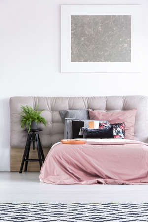 king size bed: Silver painting above the bed with black pillow and stool