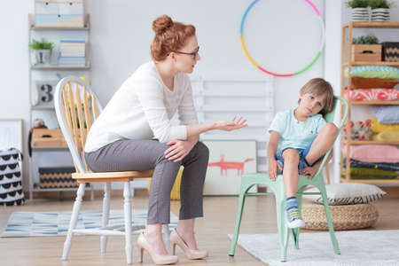 Red haired counselor talking with worried boy sitting on mint chair in colorful room with toys