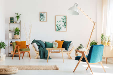 Blue chair and design lamp in natural living room with plants and two paintings on white wall