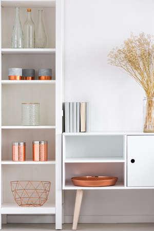 銅板銅アクセサリーと高い棚の横で白い食器棚のガラス花瓶の花 写真素材 - 85134114