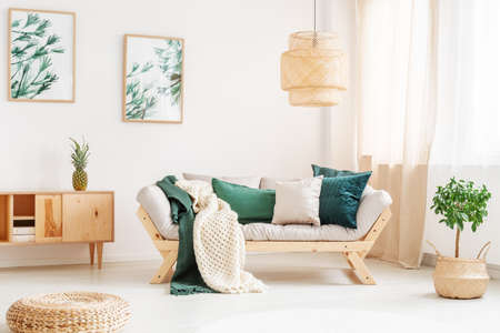 Small tree in braided basket next to sofa with green pillows and knit blanket in relax room with pouf Stockfoto