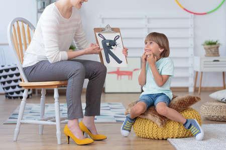 Garçon faisant de l'exercice de prononciation correcte pendant une leçon avec un orthophoniste Banque d'images - 85165128