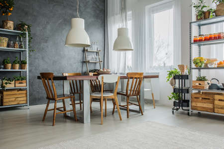 Cozy loft with dinning table, chairs and metal storage racks 写真素材