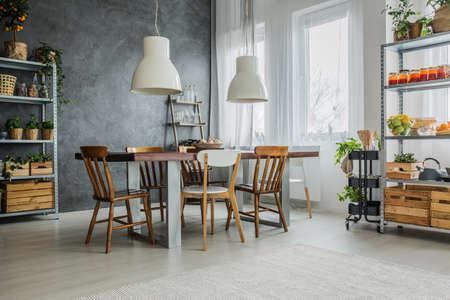 Gezellige loft met eettafel, stoelen en metalen magazijnstellingen