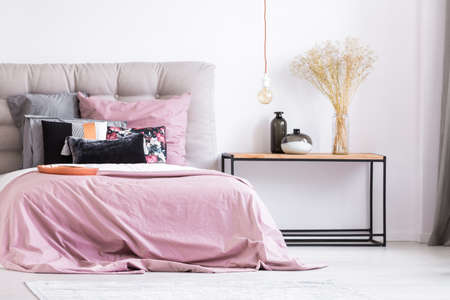 king size bed: Decorative vases and flowers on table in pastel pink bedroom with copper plate and patterned pillows on king-size bed
