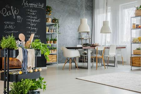 현대 다락방에 허브와 칠판 벽이 달린 주방 카트 스톡 콘텐츠