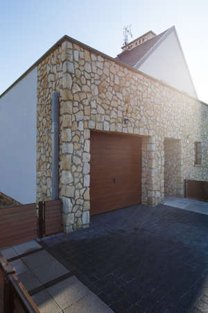 Garage door, irregular stone wall and driveway on sunny day