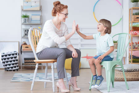 Young boy and counselor having fun during conversation in colorful room with toys Stockfoto
