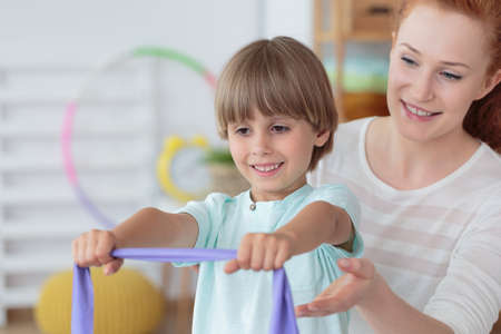 Physiotherapist and young boy practicing with an elastic band in rehabilitation room with accessories Фото со стока