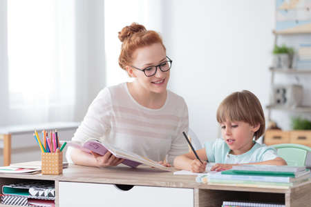 Smiling mother helping her son with math exercises while sitting at desk with notebooks