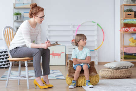 Young boy sitting on yellow pouf refusing to listen to his psychotherapist during session in a classroom