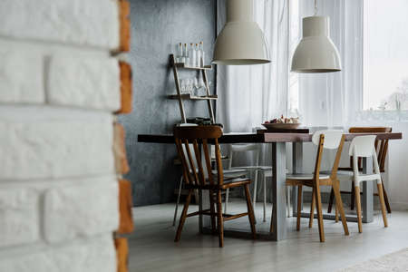 Chic dining room design with concrete wall and industrial chairs Stock Photo