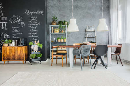 黒板のアクセントおよび折衷的なダイニング ルームで不一致の椅子 写真素材