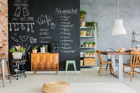 Dining room with chalkboard wall, wooden chest and kitchen cart Фото со стока - 85134313